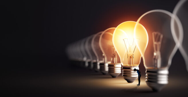 woman looking for something in the light of a lightbulb