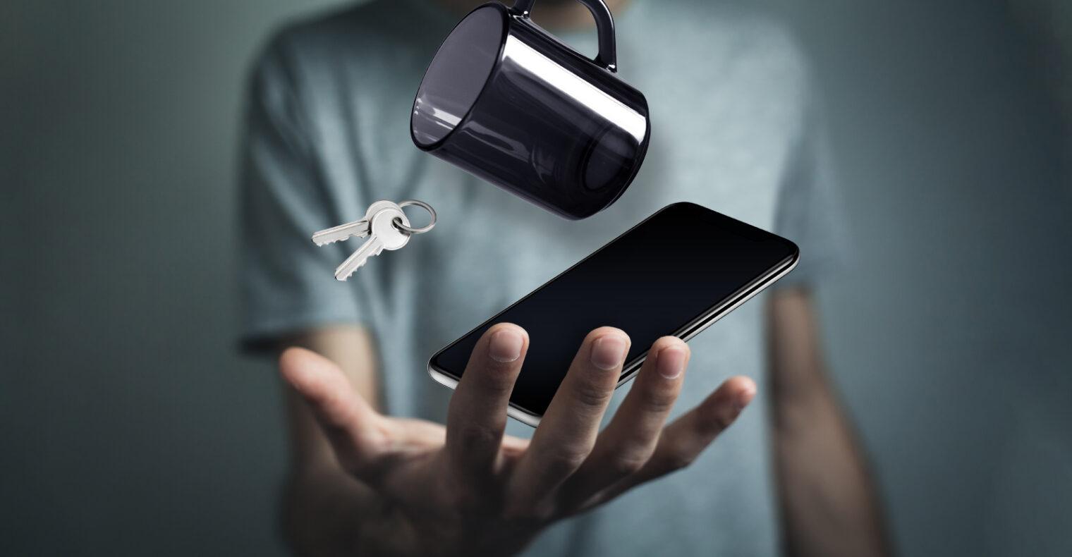keys, mug and phone falling into a hand